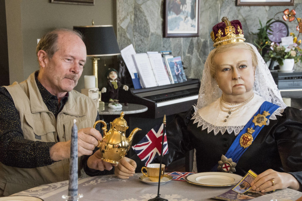 Ken Lane, former director of the Royal London Wax Museum, pours tea for Queen Victoria in his Saanich home. (Nina Grossman/News Staff)