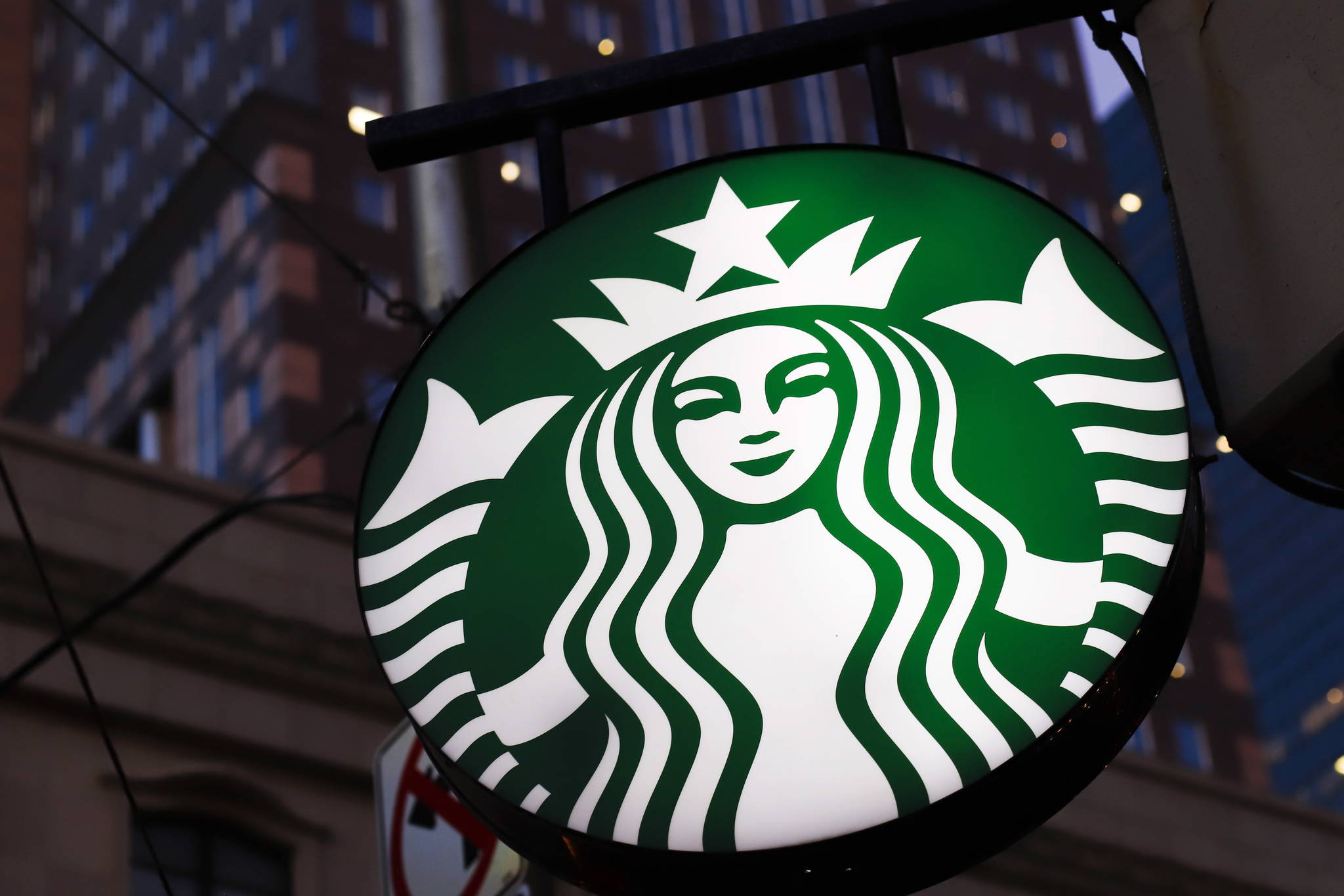 This June 26, 2019, photo shows a Starbucks sign outside a Starbucks coffee shop in downtown Pittsburgh. Starbucks customers in Canada will soon be able to down fake meat with their Frappuccinos. The coffee chain said Wednesday, Feb. 26, 2020, that it will soon start selling a sandwich featuring a meat-free patty from Beyond Meat, the El Segundo, California-based company whose patties are already found at other fast food chains. (AP Photo/Gene J. Puskar)
