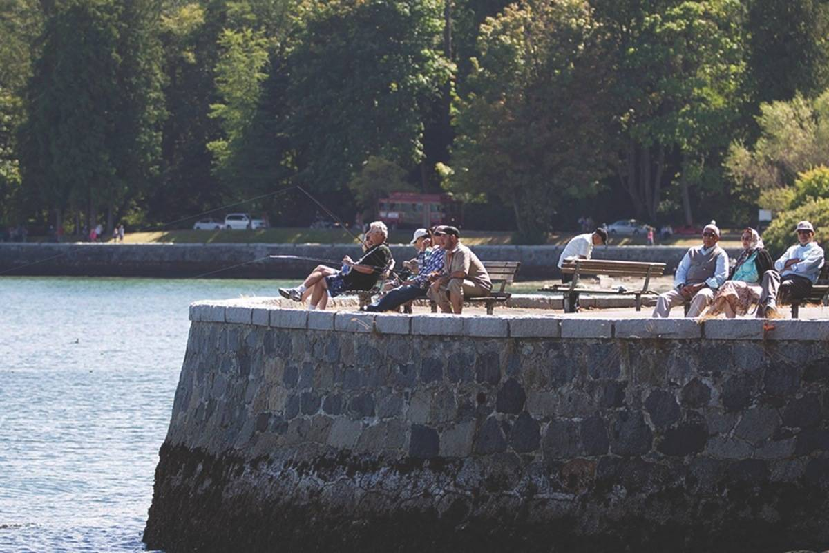 People sit along the Stanley Park seawall as others fish in Vancouver, B.C., on Sunday, August 25, 2013. THE CANADIAN PRESS/Darryl Dyck