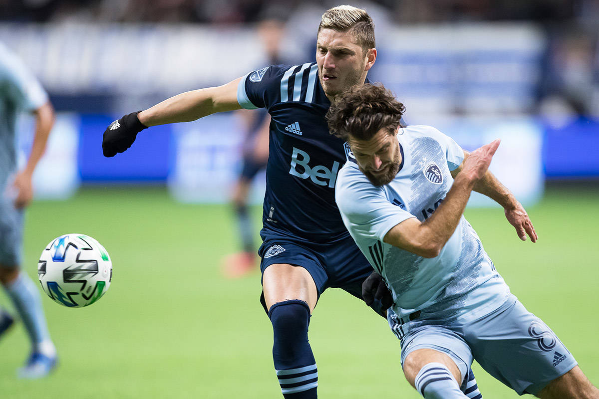 Vancouver Whitecaps' David Milinkovic, back left, and Sporting Kansas City's Graham Zusi vie for the ball during the first half of an MLS soccer game in Vancouver, B.C., Saturday, Feb. 29, 2020. THE CANADIAN PRESS/Darryl Dyck