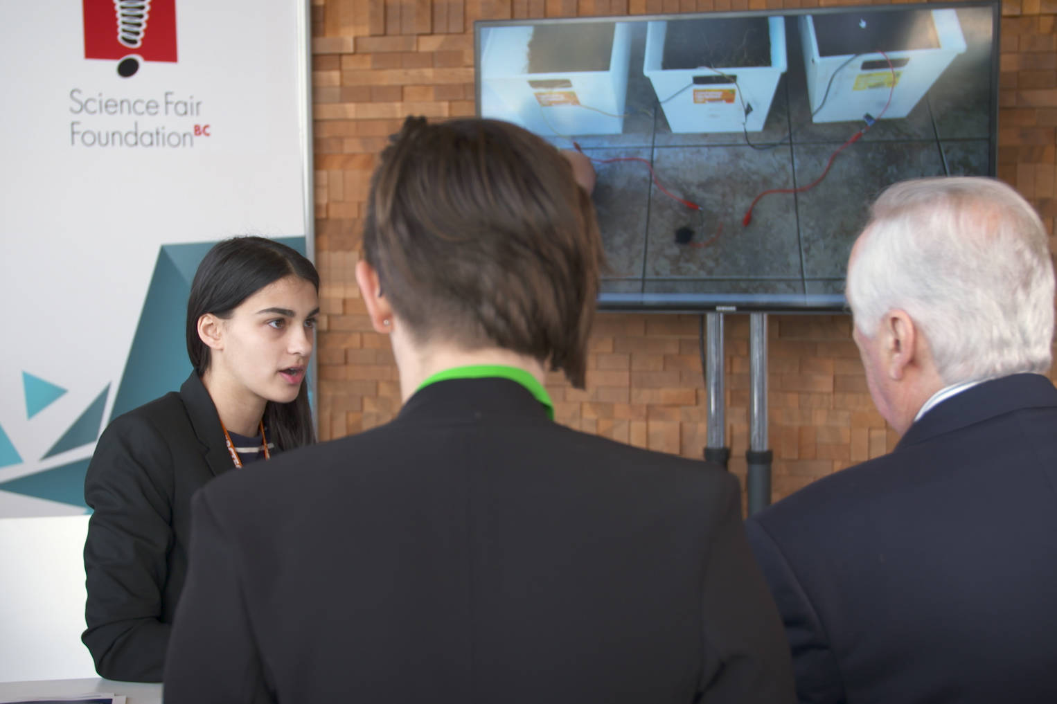 Prince Rupert's Aaliyah Mahboubi (left) explaining her microbe-powered mobile energy innovation (pictured behind her). Submit your selfie video for a chance to present at this year's Youth Innovation Showcase!
