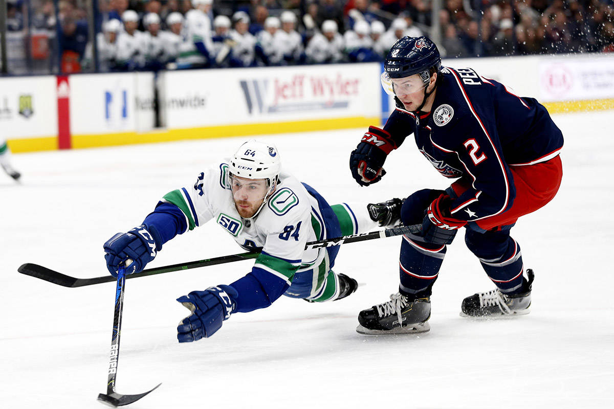 Vancouver Canucks' Tyler Motte, left, dives for the puck as Columbus Blue Jackets' Andrew Peeke defends during the first period of an NHL hockey game Sunday, March 1, 2020, in Columbus, Ohio. (AP Photo/Jay LaPrete)