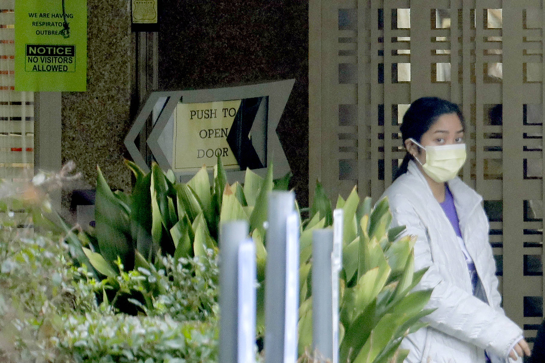 FILE - A person wearing a mask walks past a sign banning visitors at the Life Care Center in Kirkland, Wash., near Seattle, Monday, March 2, 2020. Dozens of people associated with the facility are reportedly ill with respiratory symptoms or hospitalized and are being tested for the COVID-19 virus. (AP Photo/Ted S. Warren)