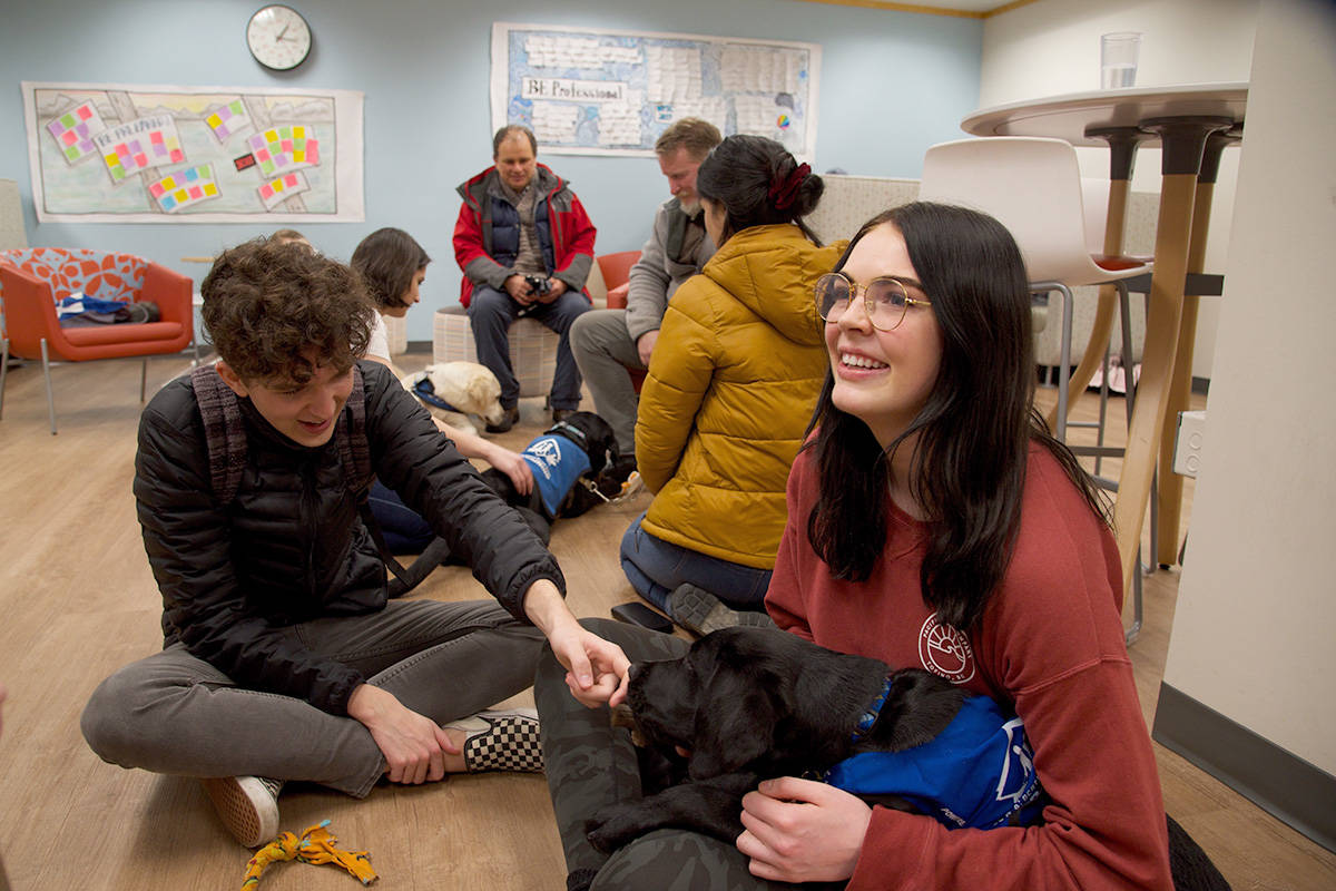 UVic students Adam Gale and Mikayla Sprung play with Archie, a BC & Alberta Guide Dog in training. (Nicole Crescenzi/News Staff)
