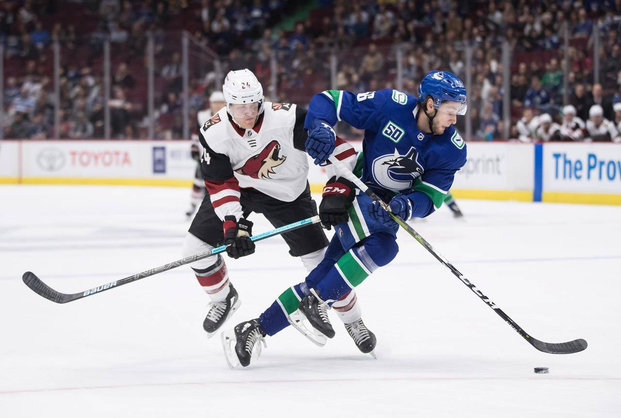 Arizona Coyotes right wing Hudson Fasching, left, and Vancouver Canucks defenceman Guillaume Brisebois collide during the first period of a pre-season NHL hockey game in Vancouver on September 26, 2019. The Vancouver Canucks have recalled defencemen Guillaume Brisebois and Jalen Chatfield from Utica of the American Hockey League under emergency conditions. The Canucks also announced forward Justin Bailey has been reassigned to Utica. (THE CANADIAN PRESS/Darryl Dyck)