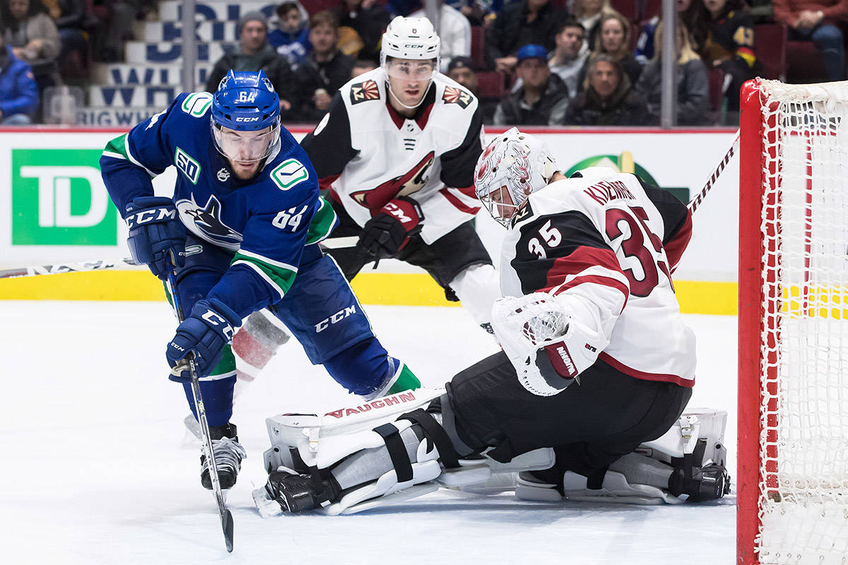 Arizona Coyotes goalie Darcy Kuemper (35) stops Vancouver Canucks' Tyler Motte (64) as Arizona's Nick Schmaltz, back, watches during the second period of an NHL hockey game in Vancouver, on Wednesday, March 4, 2020. THE CANADIAN PRESS/Darryl Dyck