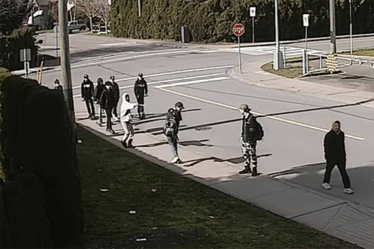 A screenshot of a home security video showing a student firing bear spray at another student on Reece Avenue next to Chilliwack secondary school on March 4, 2020. (YouTube)