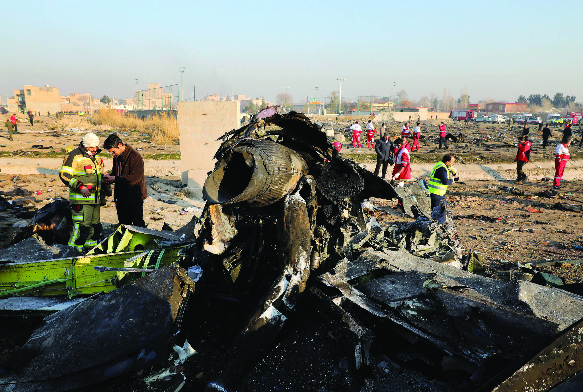 "FILE - In this Wednesday, Jan. 8, 2020 file photo debris at the scene where a Ukrainian plane crashed in Shahedshahr southwest of the capital Tehran, Iran. Two U.S. officials said Thursday that it was ""highly likely"" that an Iranian anti-aircraft missile downed a Ukrainian jetliner late Tuesday, killing all 176 people on board. President Donald Trump is suggesting he believes Iran was responsible. (AP Photo/Ebrahim Noroozi)"
