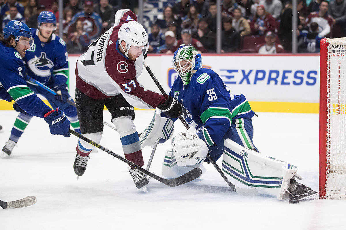 Vancouver Canucks goalie Thatcher Demko (35) stops Colorado Avalanche's J.T. Compher (37) as Vancouver's Chris Tanev, left, defends during the first period of an NHL hockey game in Vancouver, on Friday, March 6, 2020. THE CANADIAN PRESS/Darryl Dyck