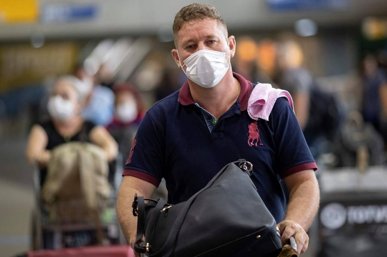 FILE - A man wears a mask as a precaution against the spread of the new coronavirus COVID-19 after his plane landed at the Sao Paulo International Airport in Sao Paulo, Brazil, Thursday, Feb. 27, 2020. (AP Photo/Andre Penner)