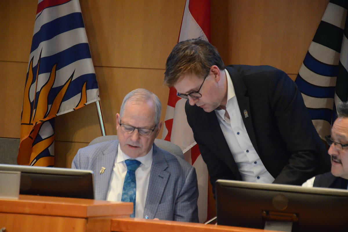 Mayor Jack Froese (seated) spoke with Coun. Eric Woodward before Woodward recused himself from discussion about demolition of properties in downtown Fort Langley. (Matthew Claxton/Langley Advance Times)