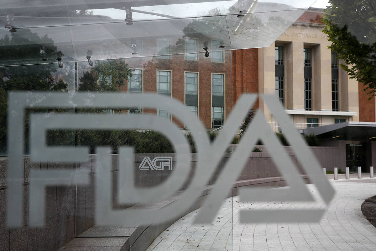 FILE - This Aug. 2, 2018, file photo shows the U.S. Food and Drug Administration building behind FDA logos at a bus stop on the agency's campus in Silver Spring, Md. U.S. regulators warned several companies to stop selling soaps, sprays and other concoctions with false claims that they can treat the new coronavirus or keep people from catching it. The warnings were emailed Friday, March 6, 2020, to companies based in the U.S., Canada and the U.K. and were announced Monday. Nearly all the targeted companies had complied by Monday morning, with mentions of the virus or products to treat it taken off their websites. (AP Photo/Jacquelyn Martin, File)