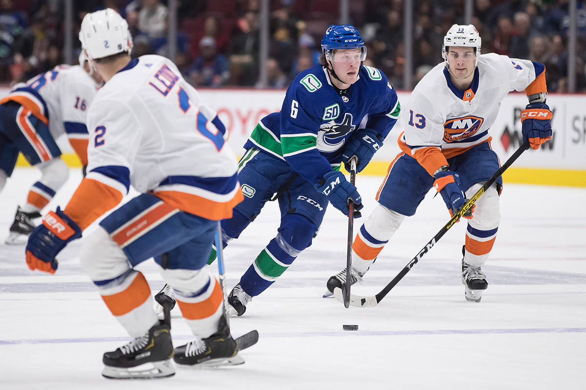 Vancouver Canucks' Brock Boeser (6) skates with the puck while being watched by New York Islanders' Mathew Barzal (13) and Nick Leddy (2) during the second period of an NHL hockey game in Vancouver, on Tuesday, March 10, 2020. THE CANADIAN PRESS/Darryl Dyck
