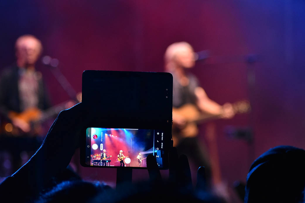 A fan takes a photo of a band at a live concert. Photo by Terry Farrell