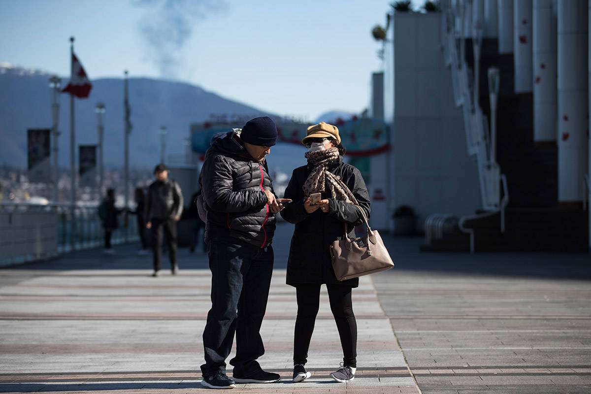 People, including a woman wearing a protective face mask stand on a nearly deserted plaza outside Canada Place, in Vancouver, on Saturday, March 14, 2020. THE CANADIAN PRESS/Darryl Dyck