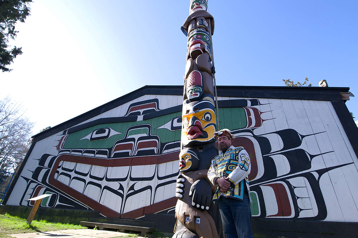 David Mungo Knox stands in front of the welcoming pole he helped restore. The pole was originally carved by his great-grandfather, Martin Mungo, his son David Martin and his niece, Mildred Hunt in commemoration of the first legal potlatch at the longhouse, which neighbours the Royal B.C. Museum. (Nicole Crescenzi/News Staff)