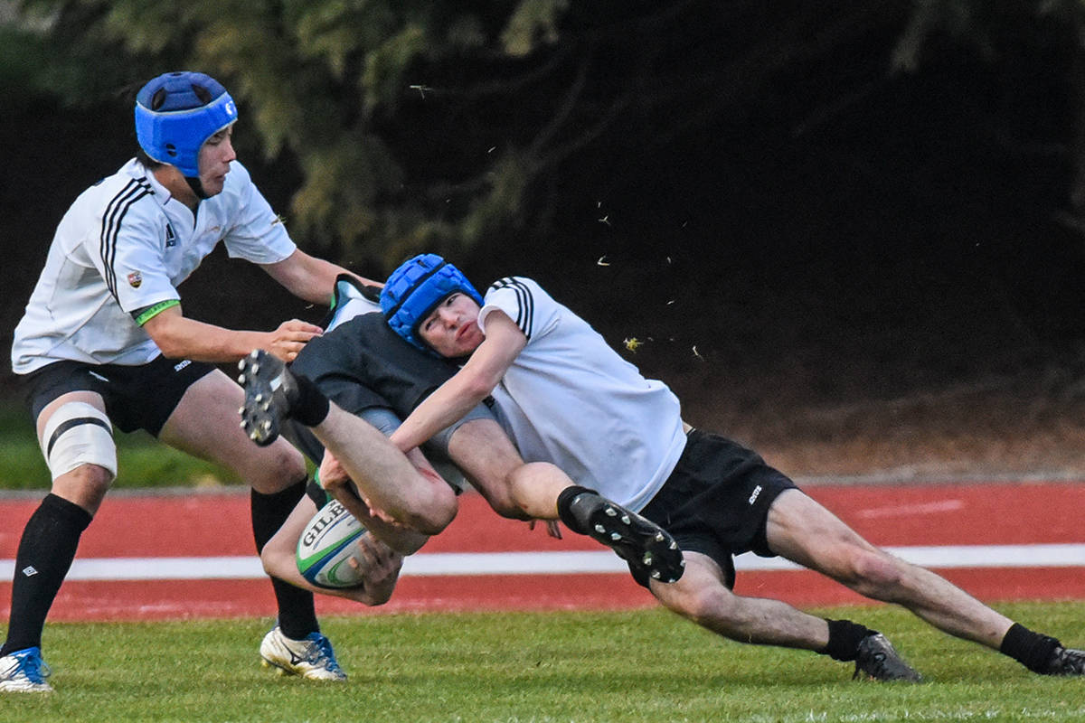 St. Michaels University School Grade 11 student Duke Curran, right, tackles an Oak Bay player during the Boot Game on Thursday, March 12. The match is likely the last rugby game of the season for the two schools. (Kyle Slavin/St. Michaels University School)