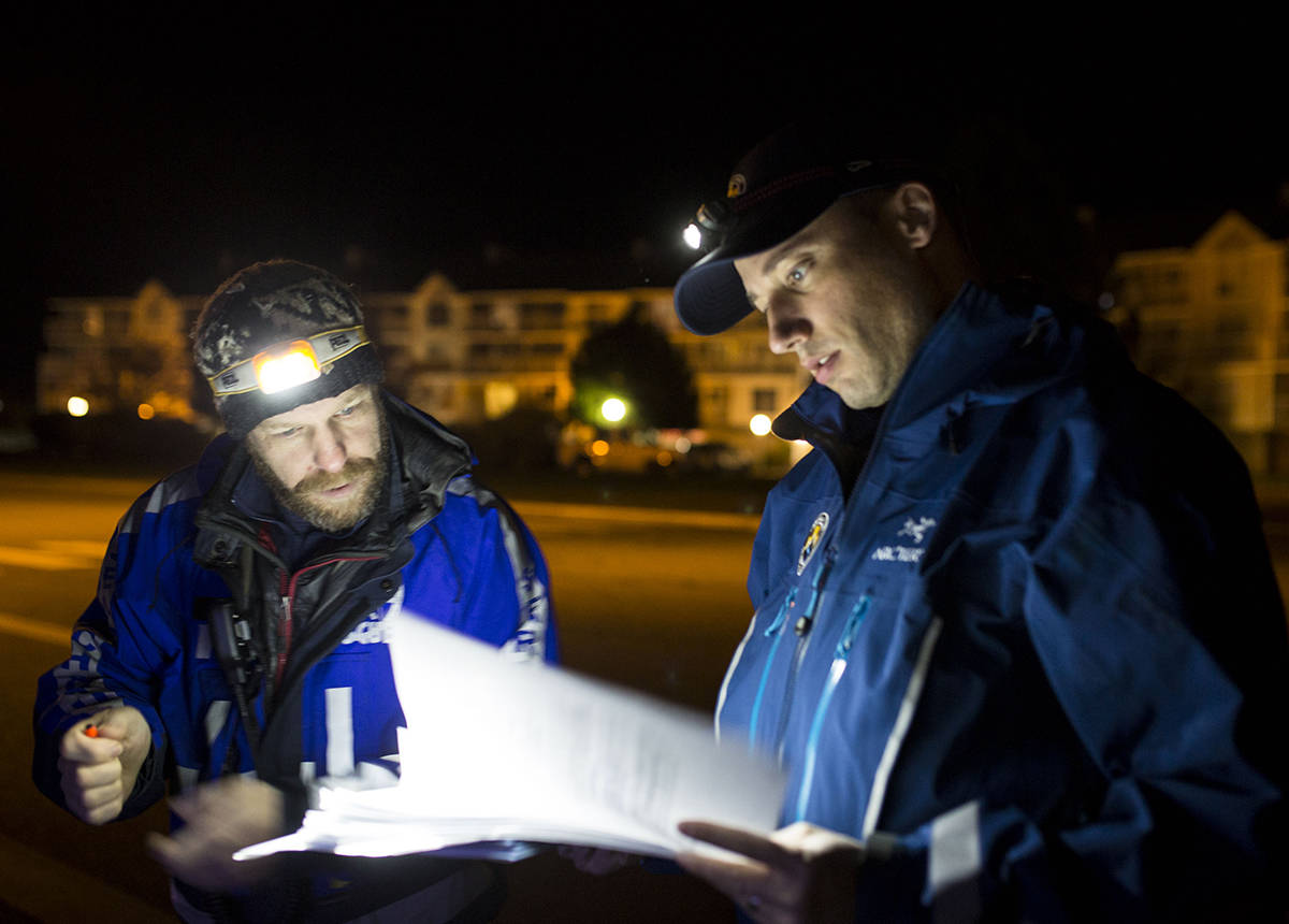 Norm Ritchie and Tyler Abbott consult their materials before starting to knock on doors in the south end of Campbell River on Oct. 29, 2019. The Campbell River Search and Rescue members were taking part in a training exercise centred around an emergency evacuation. Filep hoto by Marissa Tiel/ Campbell River Mirror