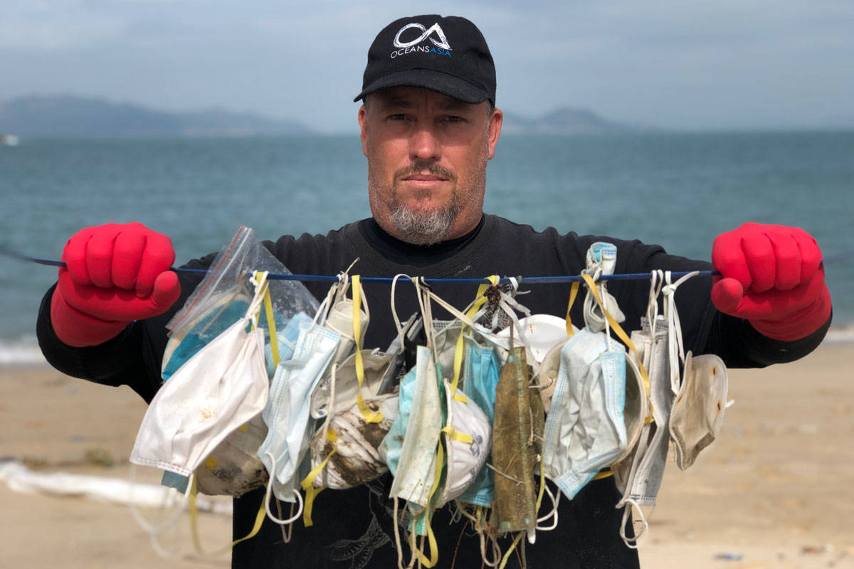 Gary Stokes, co-founder of OceansAsia, holds up a pile of surgical masks found on a beach in the Soko Islands. (Naomi Brannan/OceansAsia)
