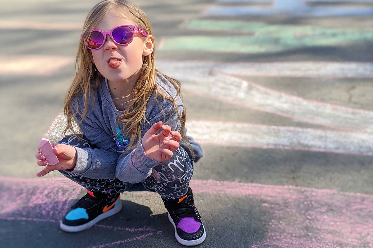 Kaila Weaver sticks her tongue out while drawing a thank-you message for Campbell River fire fighters on the sidewalk outside the Willow Point fire hall on March 19, 2020. Photo courtesy of David Weaver