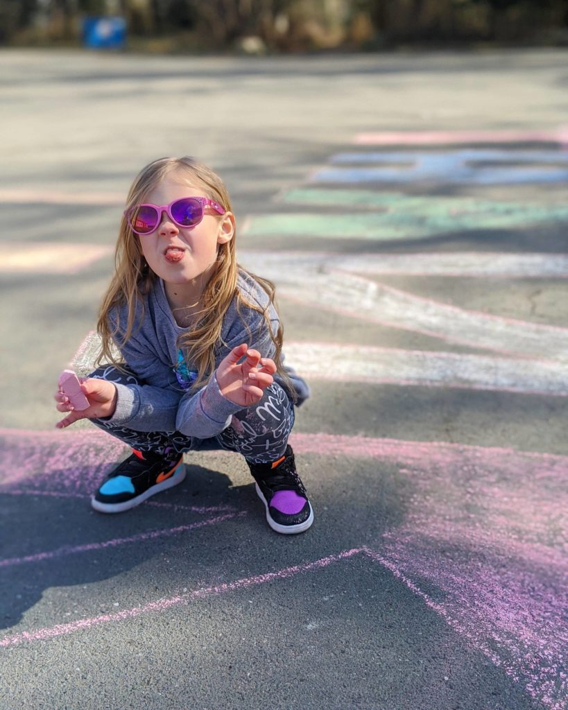 Kaila Weaver sticks her tongue out while drawing a thank-you message for Campbell River fire fighters on the sidewalk outside on March 19, 2020. Photo courtesy of David Weaver