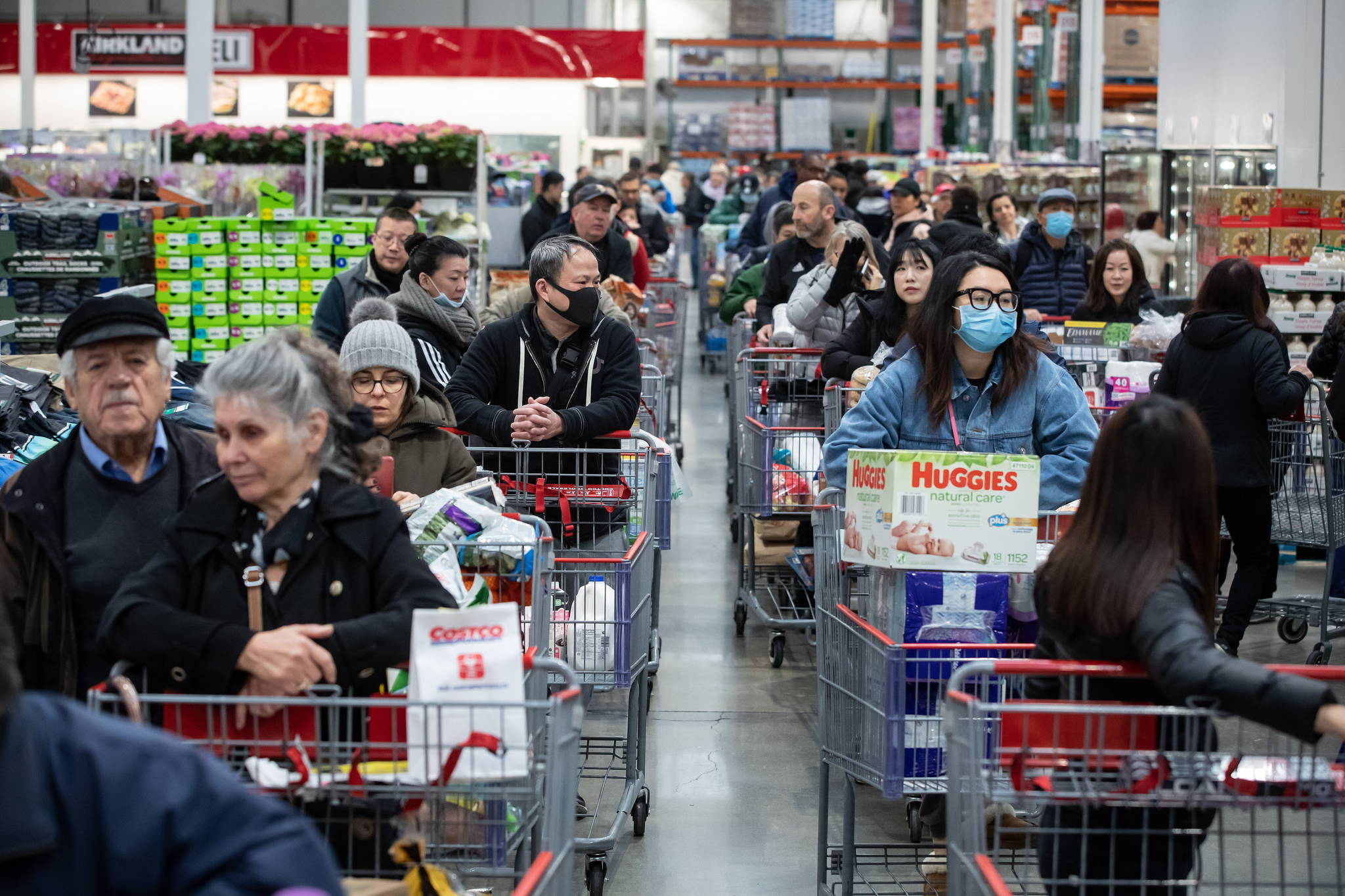 Hundreds of people queued in multiple lines waiting to pay for their purchases at a Costco store, amid concerns about the spread of the coronavirus, in Burnaby on March 16. (THE CANADIAN PRESS/Darryl Dyck)