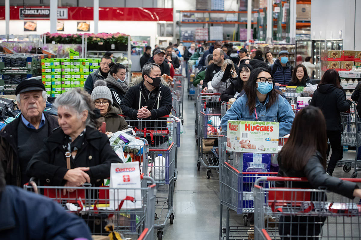 Some of the hundreds of people queued in multiple lines wait to pay for their purchases at a Costco store, amid concerns about the spread of the coronavirus, in Burnaby, B.C., on Monday, March 16, 2020. Prime Minister Justin Trudeau has announced the closure of Canada's border to those who aren't Canadian citizens or permanent residents to slow the spread of COVID-19. THE CANADIAN PRESS/Darryl Dyck