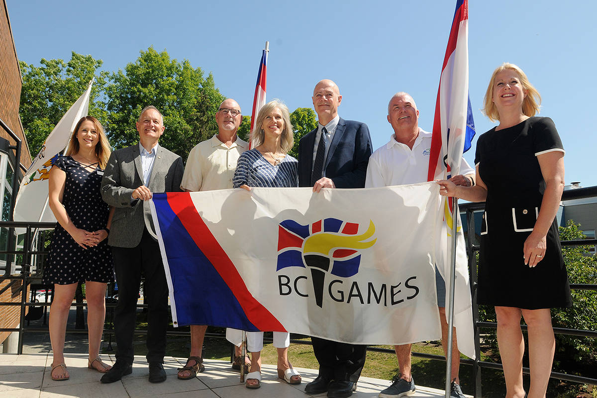 From left school board trustee Colette Trudeau, Maple Ridge Mission MLA Bob D'Eith, Maple Ridge 2020 BC Summer Games vice president Tom Bowen, president and CEO of the BC Summer Games Society Alison Noble, Maple Ridge Mayor Mike Morden, Maple Ridge 2020 BC Summer Games president Mike Keenan and Maple Ridge Pitt Meadows MLA Lisa Beare with the BC Summer Games flag that will be hanging outside city hall for the games that begin July 23, 2020. (Colleen Flanagan/THE NEWS)