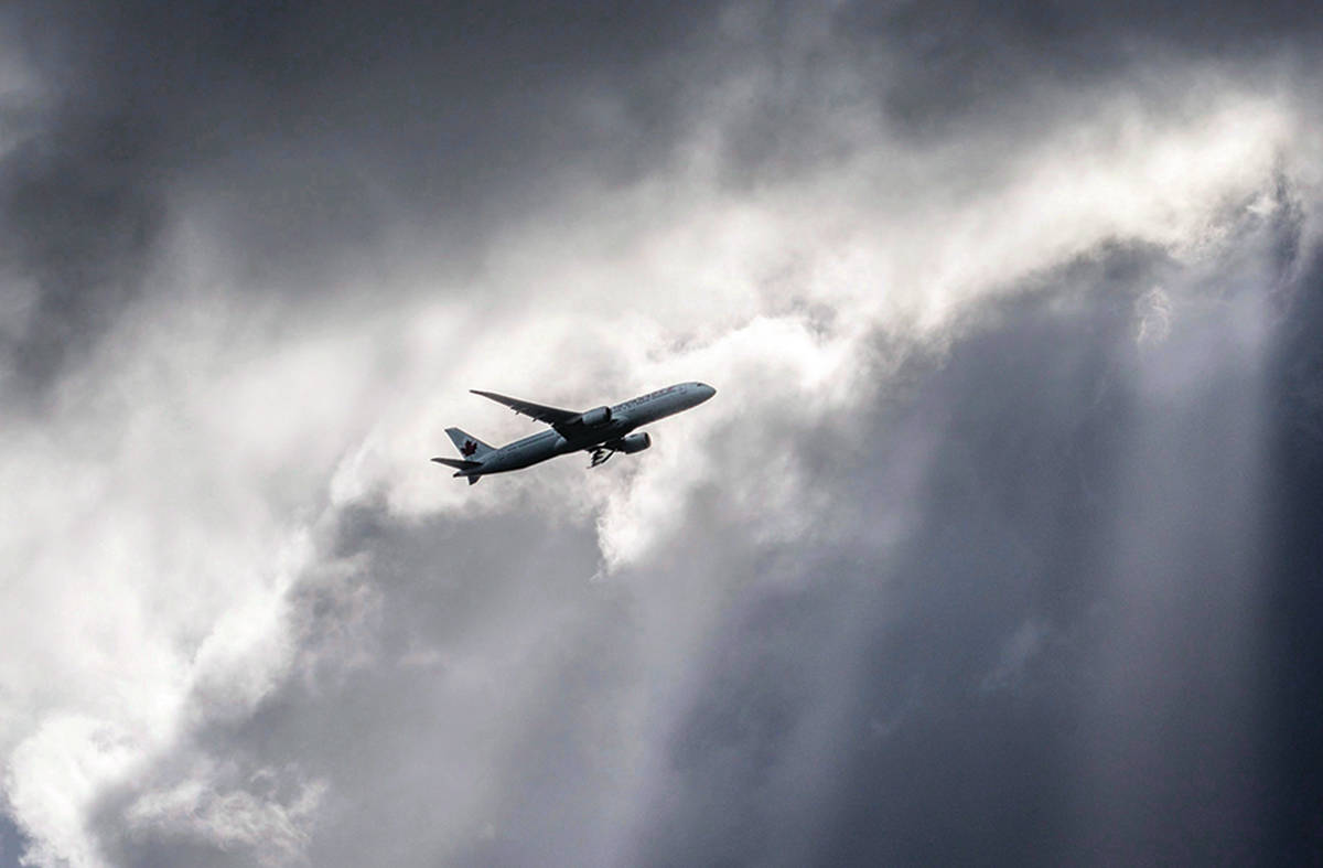 An Air Canada plane flies underneath dark clouds illuminated by some sun rays above Frankfurt, Germany, Thursday, March 2, 2017. Air Canada said Thursday it will launch its own loyalty rewards plan in 2020 and not renew its contract with the company running Aeroplan, sending Aimia's stock plummeting by more than 50 per cent and angering some points collectors.THE CANADIAN PRESS/AP-Frank Rumpenhorst/dpa via AP