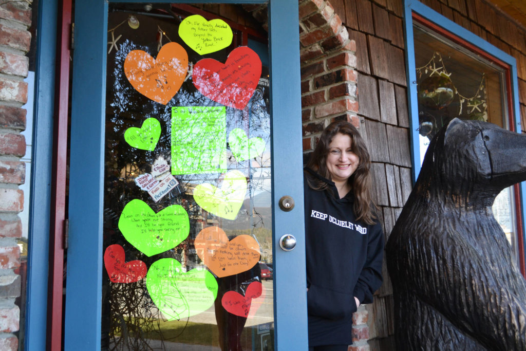 Image West Gallery co-owner Courtney Johnson lends a smile beside her melodious door collage of hearts. As of March 20, the Ucluelet gift shop that has been in business for 30 years closed indefinitely. (Nora O'Malley photo)