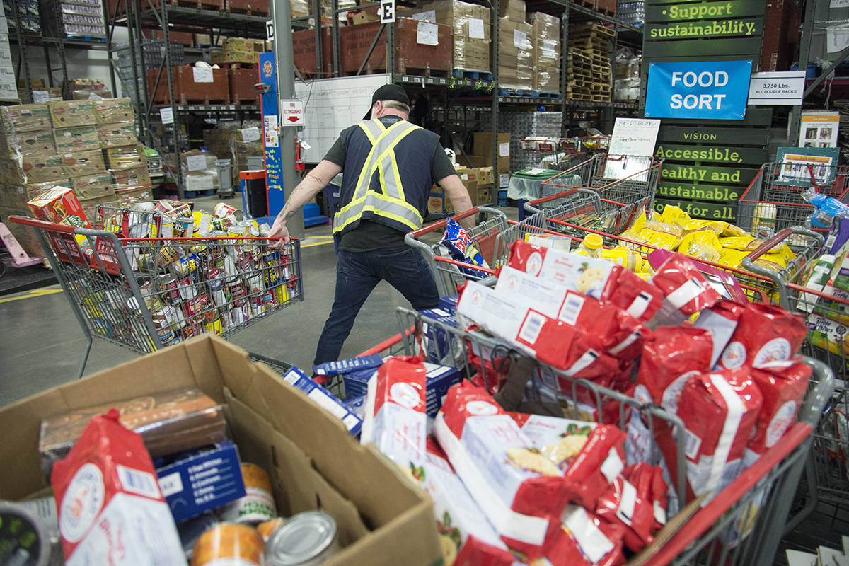 FILE – Staff are seen preparing food at the Greater Vancouver Food Bank in Burnaby, B.C. Wednesday, March 18, 2020. THE CANADIAN PRESS/Jonathan Hayward