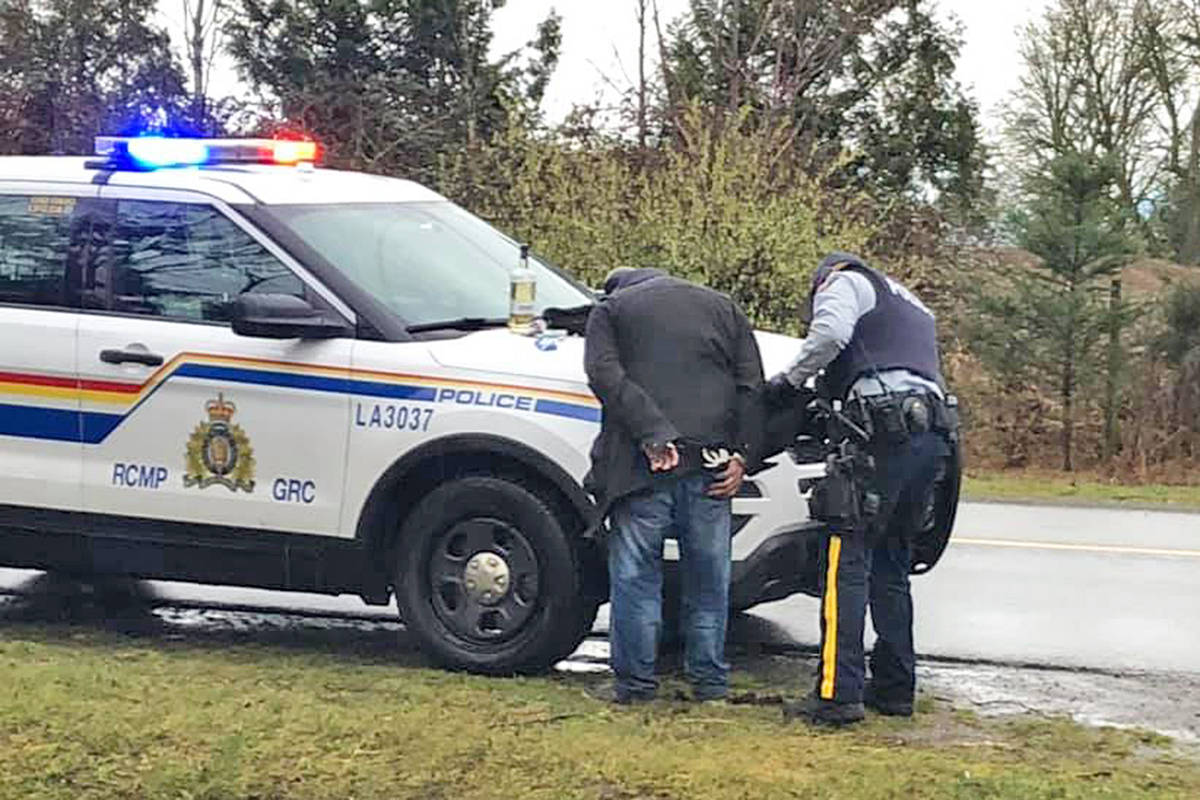A Langley RCMP officer interrogates one of two suspects caught red-handed break-in at the LQMA track in Aldergrove on Saturday, March 28th. One had a bottle of hard liquor in his possession. (LQMA/special to Langley Advance Times)