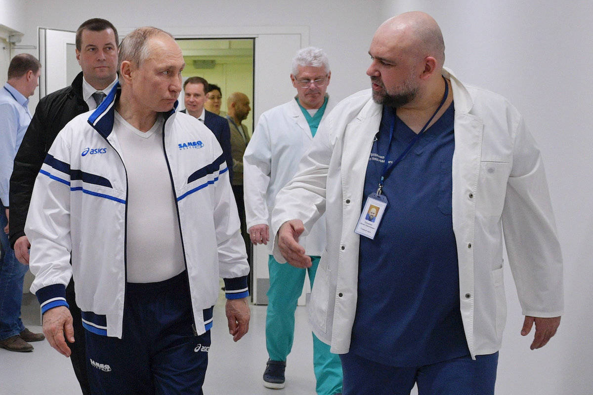 FILE - In this file photo taken on Monday, March 23, 2020, Russian President Vladimir Putin, center, and the hospital's chief Denis Protsenko, right, walk in to the hospital for coronavirus patients in Kommunarka, outside Moscow, Russia. The chief doctor of Moscow's top hospital for coronavirus patients says he has tested positive for the virus, a statement that comes a week after his encounter with President Vladimir Putin. Putin visited the Kommunarka hospital on March 23. (Alexei Druzhinin, Sputnik, Kremlin Pool Photo via AP, File)