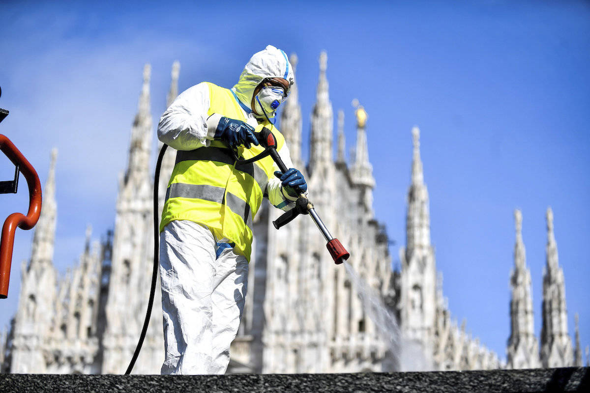 A worker sprays disinfectant to sanitize Duomo square, as the city main landmark, the gothic cathedral, stands out in background, in Milan, Italy, Tuesday, March 31, 2020. The new coronavirus causes mild or moderate symptoms for most people, but for some, especially older adults and people with existing health problems, it can cause more severe illness or death. (Claudio Furlan/LaPresse via AP)