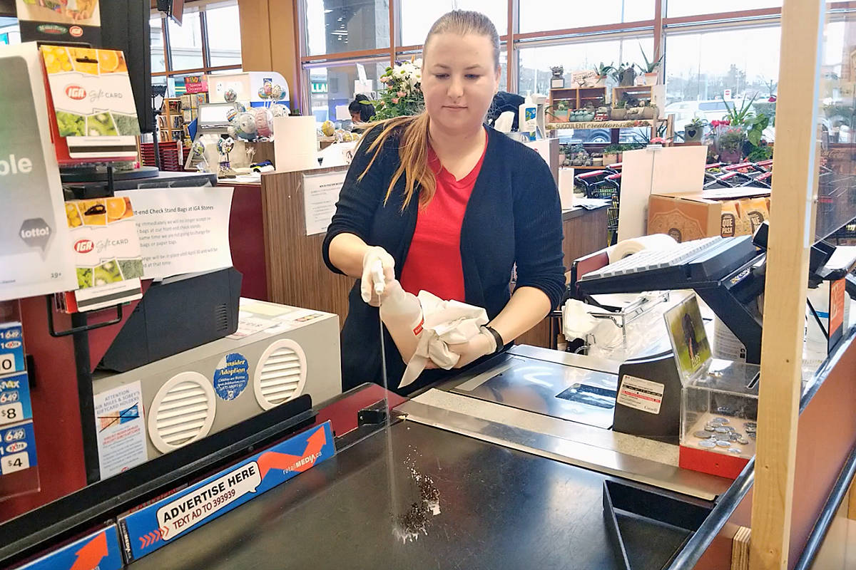 Shaylin Thulin applies disinfectant between customers at the IGA Murrayville store, which is operating under struct conditions during the COVID-19 outbreak. (Dan Ferguson/Langley Acbance Times)