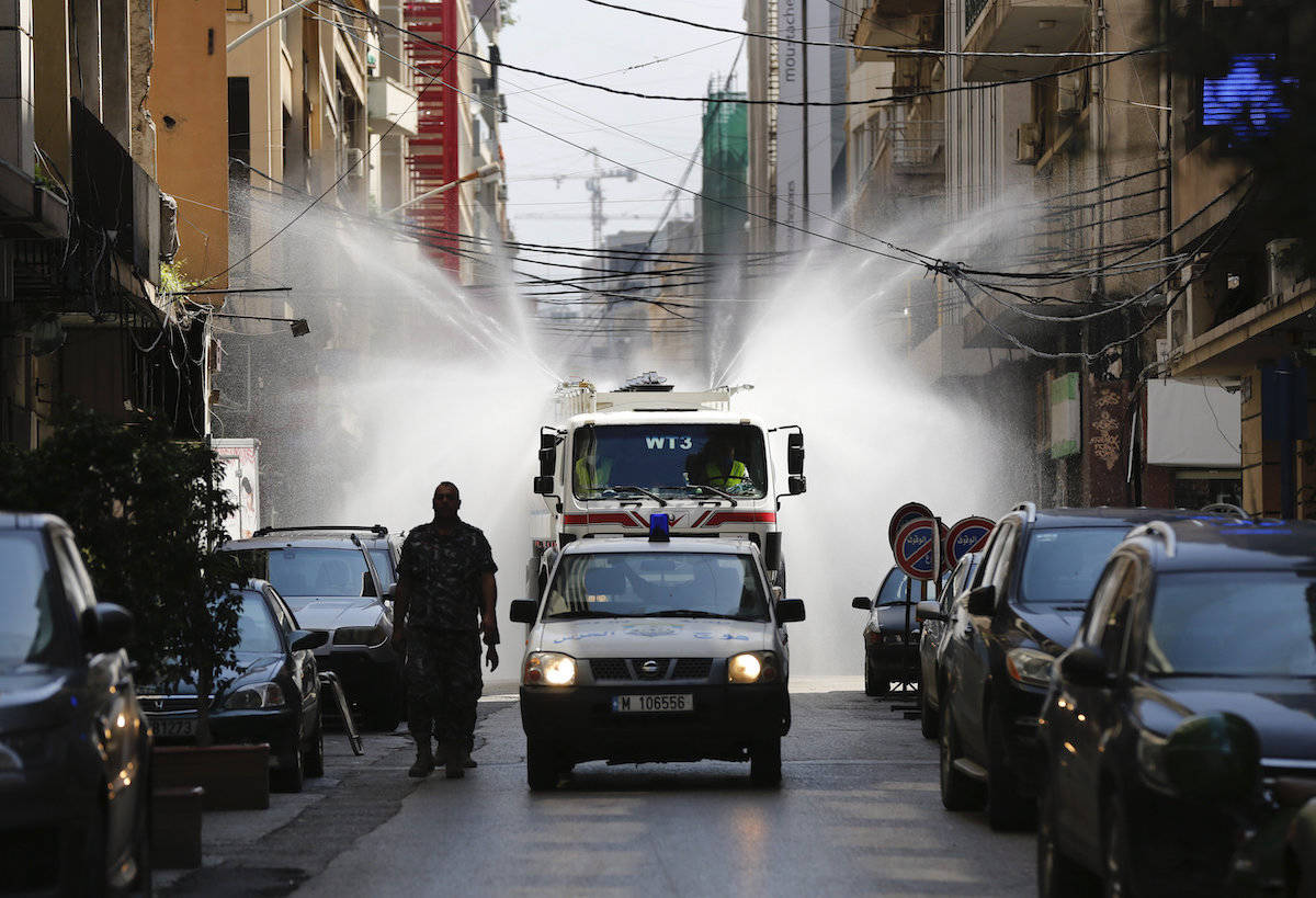 A municipal vehicle and officer lead a tanker spraying disinfectant as a precaution against the coronavirus, in Beirut, Lebanon, Thursday, April 2, 2020. (AP Photo/Hussein Malla)