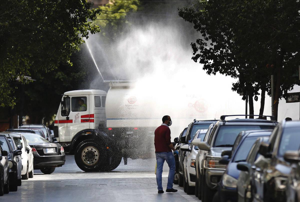 A municipal tanker sprays disinfectant as a precaution against the coronavirus, on a street in Beirut, Lebanon, Thursday, April 2, 2020. (AP Photo/Hussein Malla)