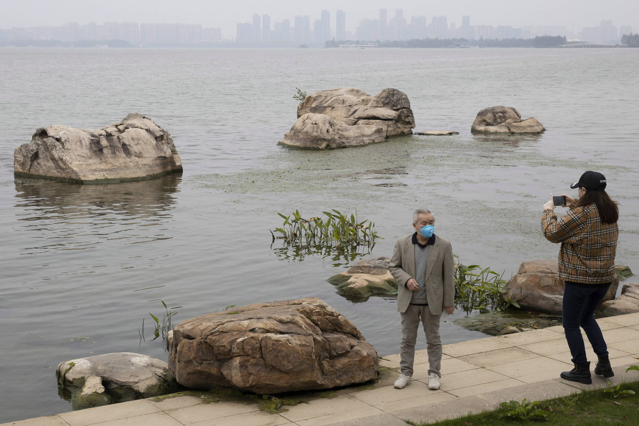 Visitors wearing mask against the coronavirus enjoy a quiet day at the East Lake park in Wuhan in central China's Hubei province on Thursday, April 2, 2020. For most people, the new coronavirus causes mild or moderate symptoms, such as fever and cough, that clear up in two to three weeks. For some, especially older adults and people with existing health problems, it can cause more severe illness, including pneumonia, and death. (AP Photo/Ng Han Guan)