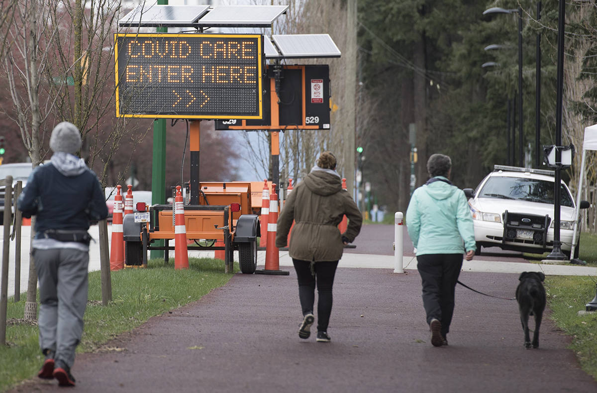 People walk past a COVID-19 testing area in Burnaby, B.C. Wednesday, April 1, 2020. THE CANADIAN PRESS/Jonathan Hayward