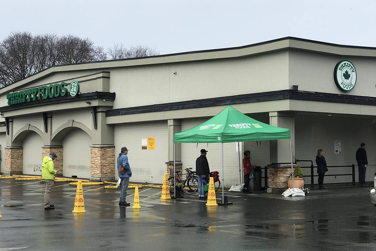 A line of customers stands on markers outside the James Bay Thrity Food's location to help stop the spread of COVID-19. (Kendra Crighton/News Staff)