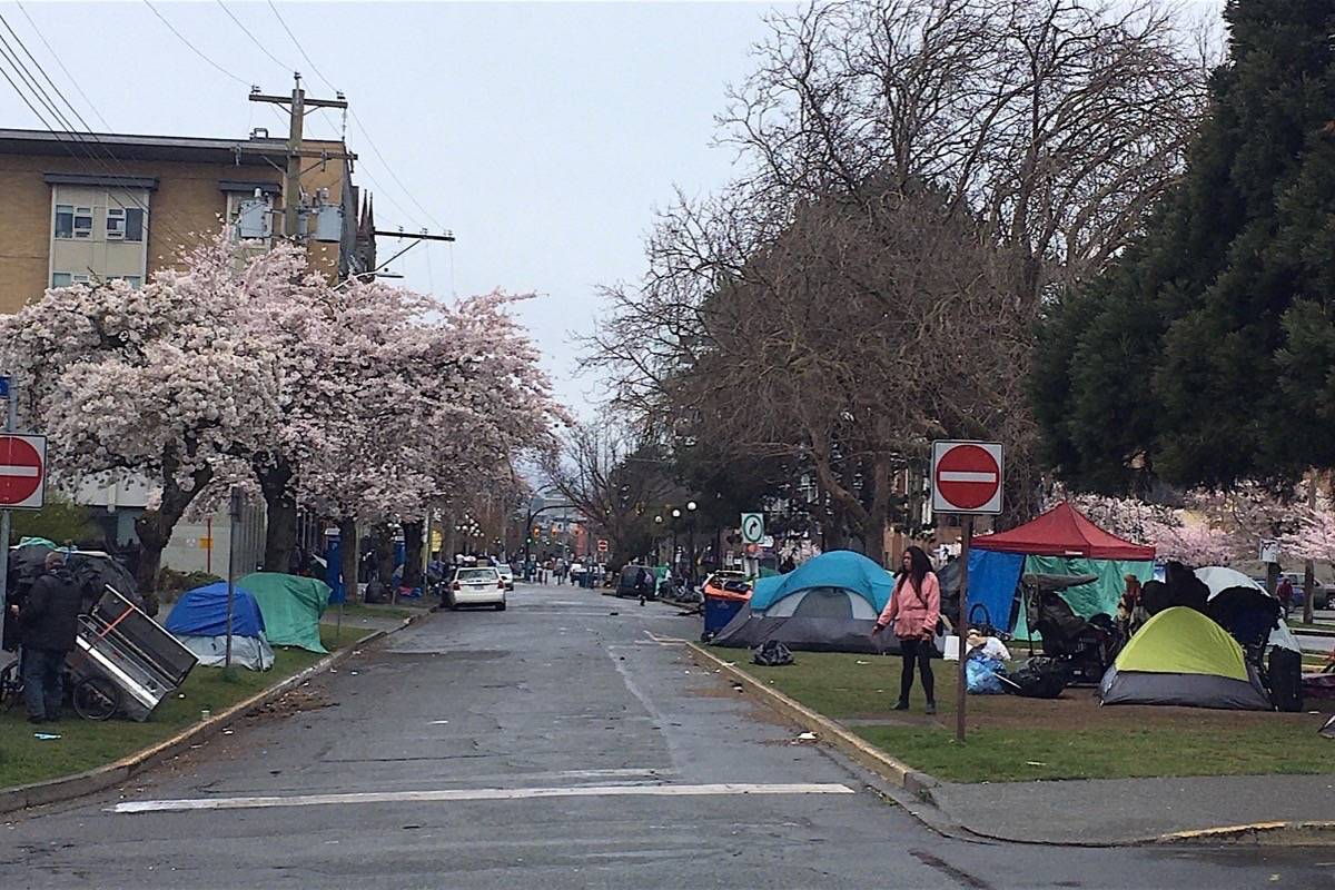 Tents stretch for blocks on Pandora Street in downtown Victoria March 26, with handouts of food, clothing and needles continuing outside a drop-in centre that has been forced to close due to COVID-19 rules. (Tom Fletcher/Black Press)