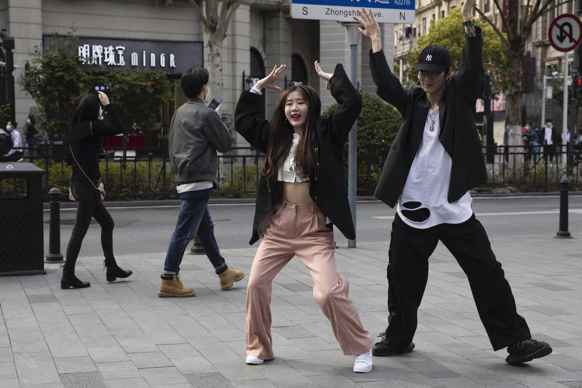 Chinese youths record a dance routine on the streets of Wuhan in central China's Hubei province on Wednesday, April 8, 2020. Streets in the city of 11 million people were clogged with traffic and long lines formed at the airport, train and bus stations as thousands streamed out of the city to return to homes and jobs elsewhere. Yellow barriers that had blocked off some streets were gone, although the gates to residential compounds remained guarded. (AP Photo/Ng Han Guan)