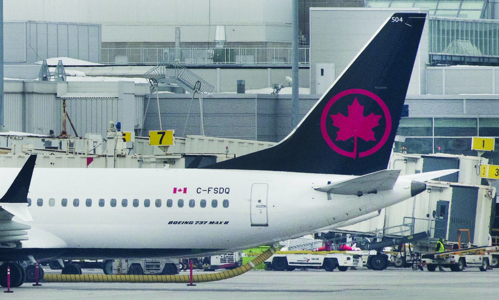 FILE – An Air Canada Boeing 737 Max 8 aircraft is shown next to a gate at Trudeau Airport in Montreal on March 13, 2019. THE CANADIAN PRESS/Graham Hughes
