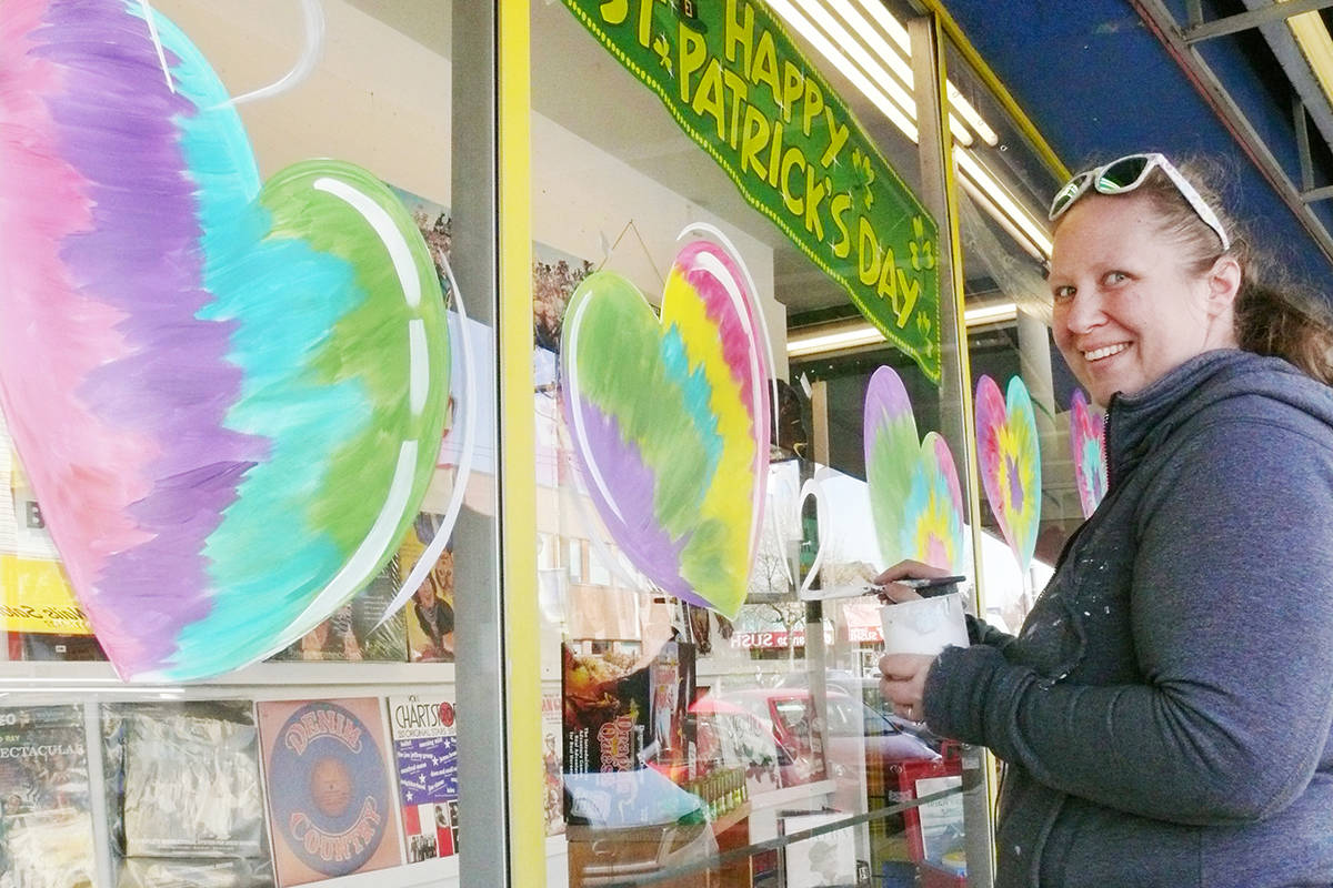 Artist Judy Pohl was painting hearts on storefront windows in Langley City on Wednesday. April 8, for the 'Community Strong' initiative launched by the Downtown Langley Business Association. (Dan Ferguson/Langley Advance Times)