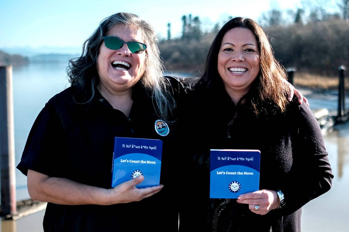 Phyllis and Fern Gabriel hold a copy of their hən̓q̓əmin̓əm̓ children's book Let's Count the Moon. (Langley Advance Times files)