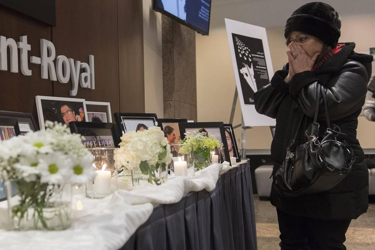 A woman pauses at a makeshift memorial prior to a ceremony in Montreal, Sunday, Jan. 19, 2020, to remember those who lost their lives in Ukraine International Airlines Flight 752 which was shot down shortly after takeoff in Iran on January 8, 2020. The investigation into Iran's downing of a commercial jetliner that killed dozens of Canadians in January has hit a snag due to COVID-19. THE CANADIAN PRESS/Graham Hughes