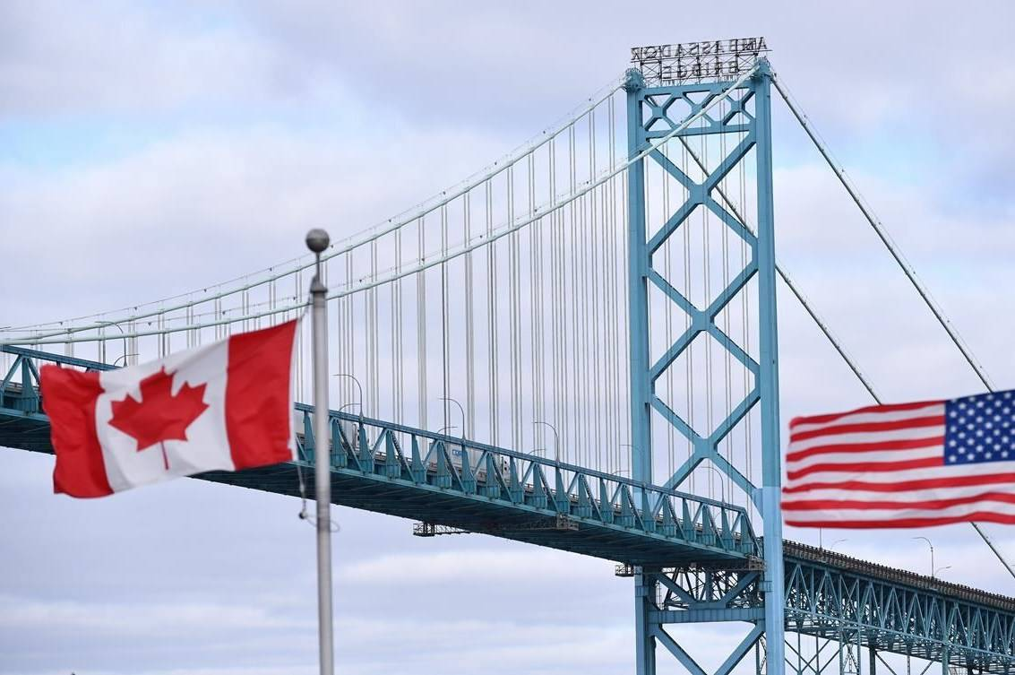 Canadian and American flags fly near the Ambassador Bridge at the Canada-USA border crossing in Windsor, Ont. on Saturday, March 21, 2020. In the time of the novel coronavirus, Canada and the United States seem to be playing to type: the friendly apologists of the Great White North coming together against a common enemy, America's combative revolutionaries threatening to tear each other apart.THE CANADIAN PRESS/Rob Gurdebeke