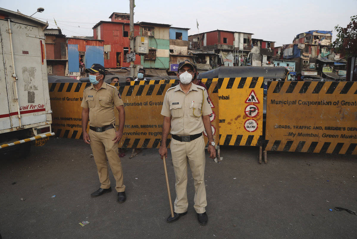 Indian policemen stand guard after a protest against the extension of the lockdown, at a slum in Mumbai, India, Tuesday, April 14, 2020. (AP Photo/Rafiq Maqbool)