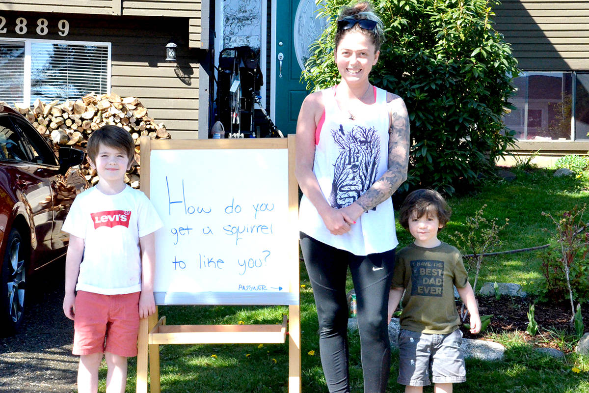 Six-year-old Langley resident Sebastian Elliott offers up a new joke on his front lawn with mom Racquel and brother Simon. (Ryan Uytdewilligen/Langley Advance Times)