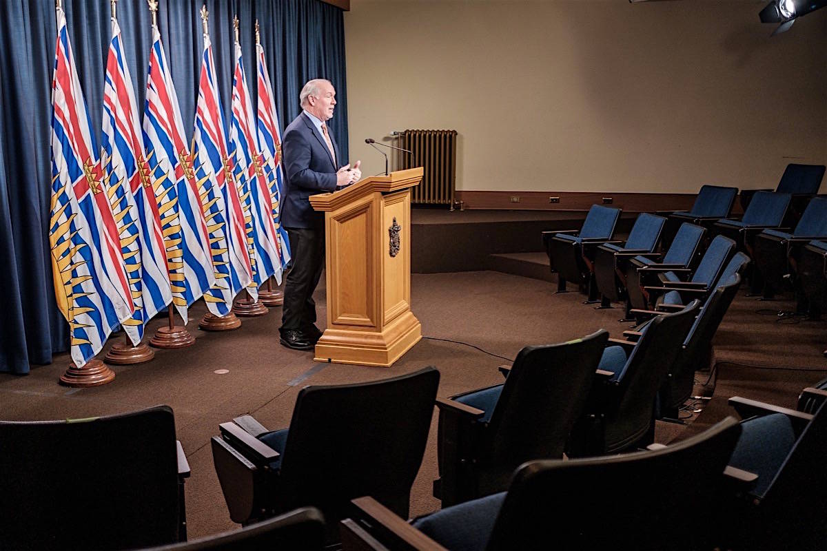 B.C. Premier John Horgan takes questions in a nearly empty B.C. legislature press theatre, April 9, 2020. (B.C. government)